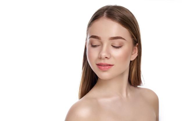Młoda, piękna modelka o zadbanej twarzy, idealnej skórze pozuje w studio