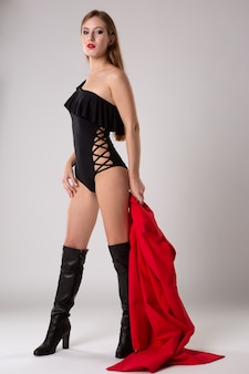 Młoda piękna modelka pozuje w czarnym seksownym body i butach na wysokich obcasach z jaskrawoczerwonym płaszczem przeciwdeszczowym, portret mody