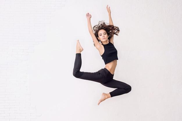 Młoda piękna modelka skacze wysoko z naturalnym makijażem i pięknymi włosami na białym tle
