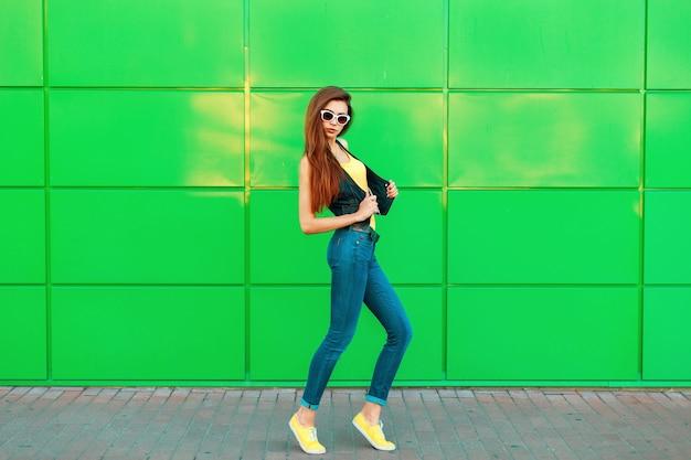 Młoda piękna modelka w stylowe modne ubrania pozuje w pobliżu zielonej jasnej ściany.