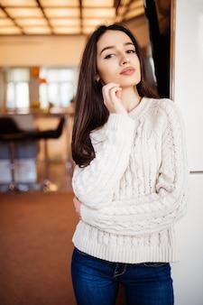Młoda piękna modelka z dużymi oczami, czerwonymi ustami i długimi brązowymi włosami w niebieskich dżinsach zostaje w pokoju w swoim domu