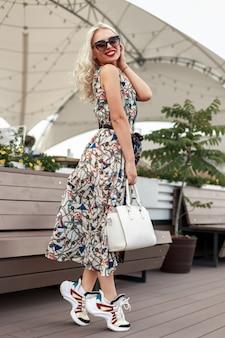 Młoda piękna modelka z fryzurą z okularami przeciwsłonecznymi w modnej sukience ze stylowymi trampkami na ulicy