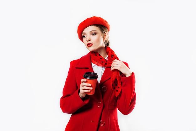 Młoda piękna modna kobieta ubrana w stylowy zimowy czerwony płaszcz, jedwabny szal i czerwony beret na białym szaliku