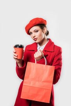 Młoda piękna modna kobieta z torbą na zakupy na sobie stylowy płaszcz zimowy czerwony, jedwabny szal i czerwony beret na białym szalikiem