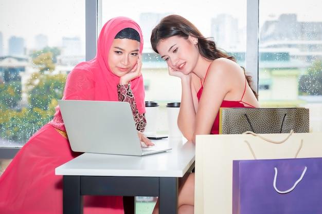 Młoda piękna muzułmanka i kaukaskie przyjaźnie z torby na zakupy i tablet ciesząc się na zakupy w kawiarni