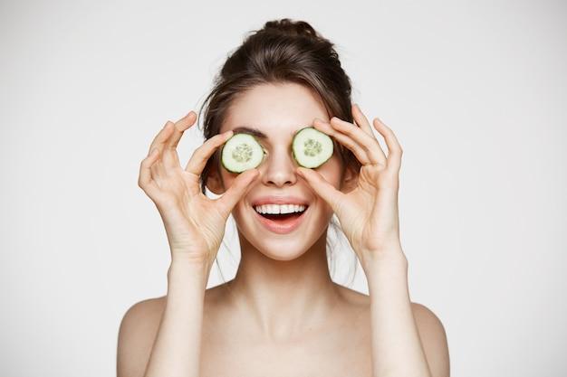 Młoda piękna naga dziewczyna uśmiecha się chujący oczy za ogórkowymi plasterkami nad białym tłem. kosmetyki do pielęgnacji skóry i kosmetologii.