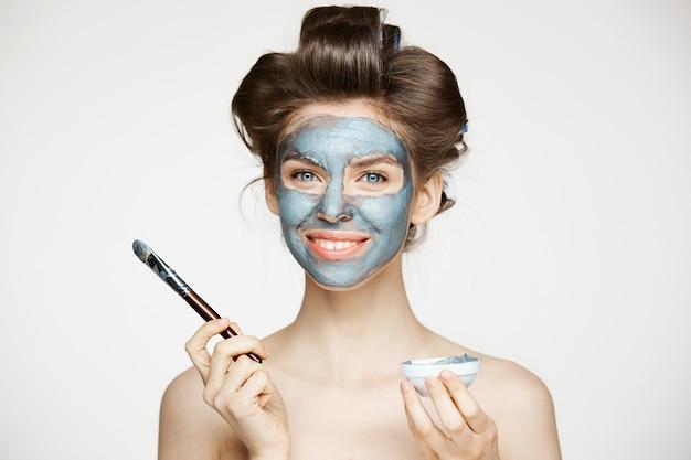 Młoda piękna naga kobieta w lokówki zakrywa twarz z mack. zabieg na twarz. kosmetyki kosmetyczne i spa.