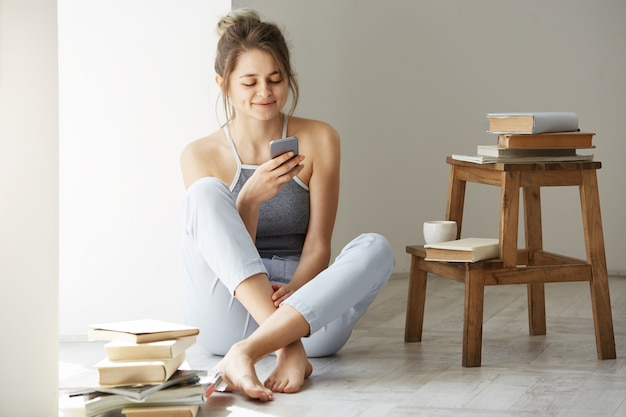 Młoda piękna nastoletnia kobieta surfuje sieć patrzeje telefonu ekranu uśmiechniętego obsiadanie na podłoga wśród starych książek blisko okno nad biel ścianą.