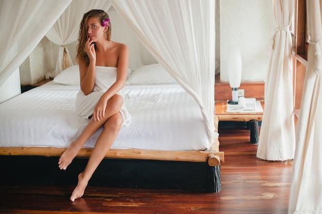Młoda piękna naturalna seksowna kobieta po prysznic, ręcznik kąpielowy, siedzi na łóżku, białe prześcieradła, tropikalny hotel, miodowy księżyc, kwiat orchidei, uśmiechnięta, romantyczna, nieśmiała, szczupłe opalone ciało, mokre włosy, kurort, zalotna
