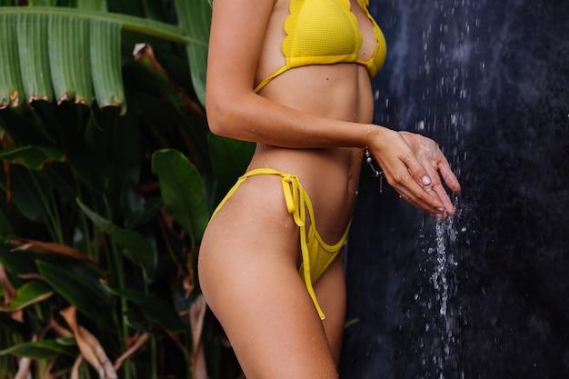 Młoda, piękna, opalona modelka z brązową skórą w żółtym bikini pod prysznicem na świeżym powietrzu