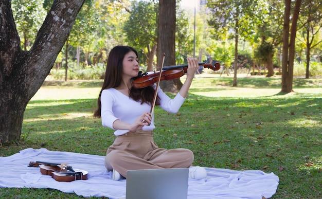 Młoda piękna pani gra na skrzypcach w parku. czas relaksu, z radosnym uczuciem