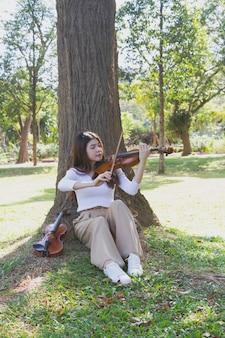 Młoda piękna pani gra na skrzypcach z szczęśliwym uczuciem