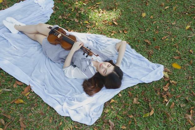 Młoda piękna pani trzyma skrzypce i bowin rękę, kładąc się na zielonym parterze z uczuciem relaksu, w parku