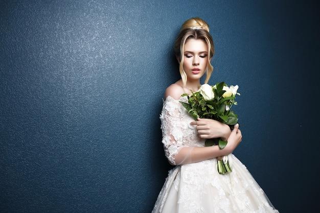 Młoda piękna panna młoda. fryzura ślubna, blond włosy, suknia ślubna, makijaż i bukiet panny młodej. strzał w pomieszczeniu