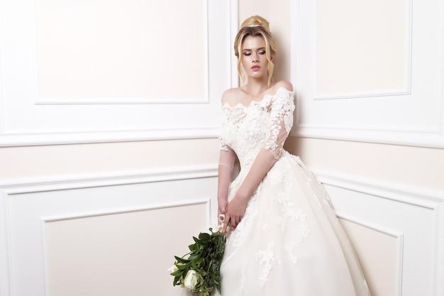 Młoda piękna panna młoda. fryzura ślubna, blond włosy, suknia ślubna, makijaż i bukiet panny młodej.