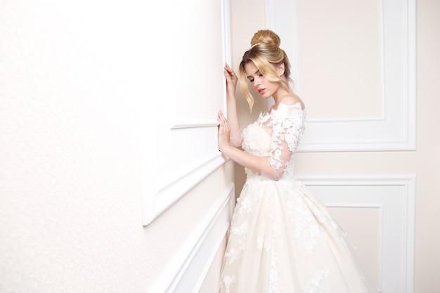 Młoda piękna panna młoda. fryzura ślubna, blond włosy, suknia ślubna, makijaż. obraz w pomieszczeniu