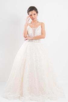 Młoda piękna panna młoda jest ubranym białą ślubną suknię.