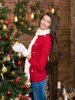 Młoda piękna panna młoda moda w zimie radosna dziewczyna kobiet w zimowe ubrania, siedząc w pobliżu choinki, trzymając pudełko.