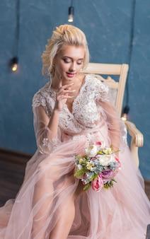 Młoda piękna panna młoda moda w zimie wystrój z bukietem kwiatów w dłoniach. piękna panna młoda portret ślubny makijaż i fryzurę.