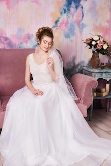 Młoda piękna panna młoda przygotowuje się do sesji zdjęciowej ślubu
