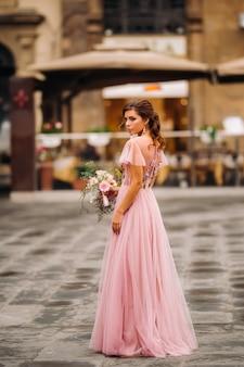 Młoda piękna panna młoda stoi w centrum starego miasta we florencji we włoszech. panna młoda w pięknej różowej sukience z bukietem w toskanii we włoszech.
