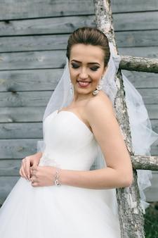 Młoda piękna panna młoda stojąc na drabinie na tle drewnianej ściany