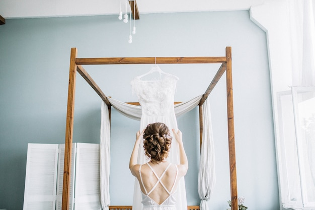 Młoda piękna panna młoda trzyma suknię ślubną