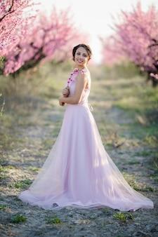 Młoda piękna panna młoda w ukwieconym ogrodzie