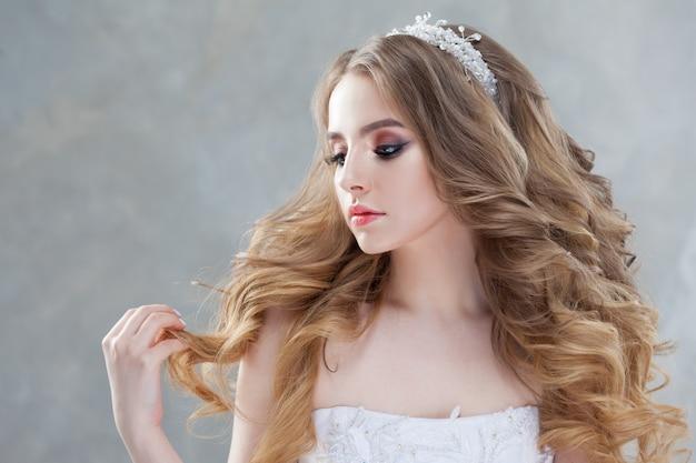 Młoda piękna panna młoda z luksusowymi lokami. fryzura ślubna z tiarą.