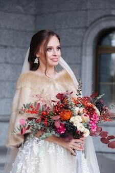 Młoda piękna panna młoda z ślubnym bukietem patrzeje strona outdoors.