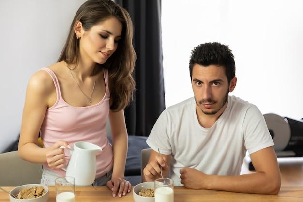 Młoda piękna para je płatki śniadaniowe z jagodami i mlekiem.