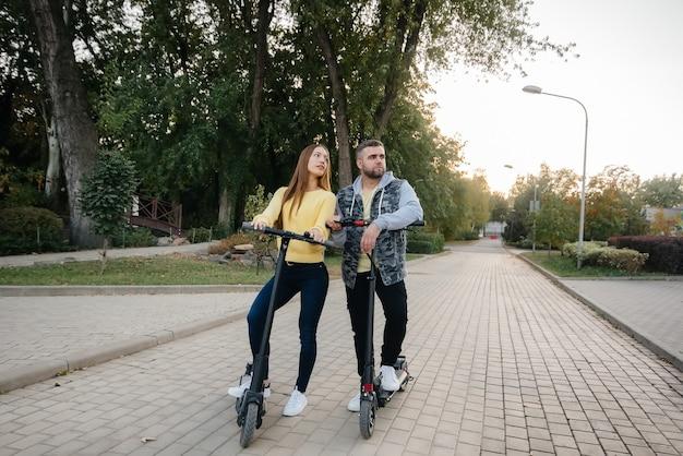 Młoda piękna para jeździ na skuterach elektrycznych w parku w ciepły jesienny dzień.