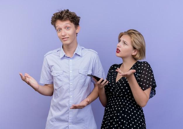 Młoda piękna para kobieta patrzy na swojego chłopaka niezadowolona z aems, pytając go, podczas gdy jej chłopak wygląda na zdezorientowanego i nie ma odpowiedzi na niebiesko