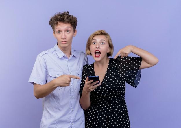 Młoda piękna para kobieta trzymając smartfon i wskazując palcem na smartfonie ze swoim chłopakiem stojącym na niebieskiej ścianie