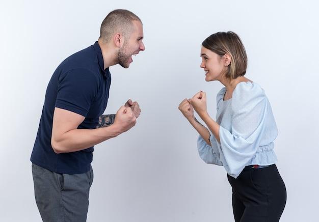 Młoda piękna para mężczyzna i kobieta kłócą się krzycząc z zaciśniętymi pięściami stojąc nad białą ścianą