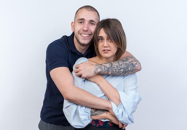 Młoda piękna para mężczyzna i kobieta obejmująca szczęśliwą i pozytywną uśmiechniętą pozycję nad białą ścianą