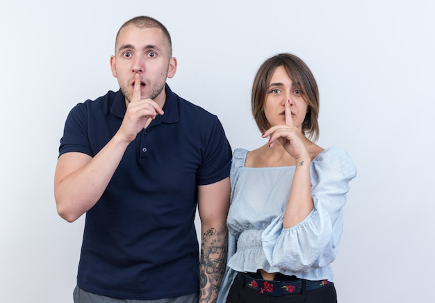 Młoda piękna para mężczyzna i kobieta patrząca robiąc gest ciszy z palcami na ustach stojących