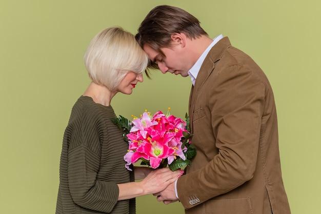 Młoda piękna para, mężczyzna i kobieta szczęśliwi w miłości trzymając bukiet kwiatów z okazji międzynarodowego dnia kobiet stojąc na zielonej ścianie
