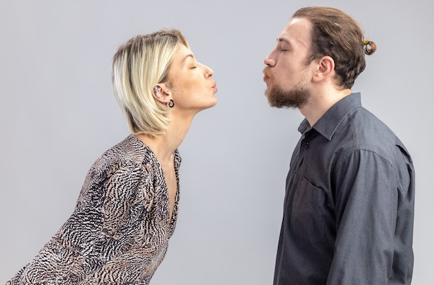 Młoda piękna para mężczyzna i kobieta szczęśliwy w miłości będzie się całować obchodzi walentynki stojąc na białej ścianie
