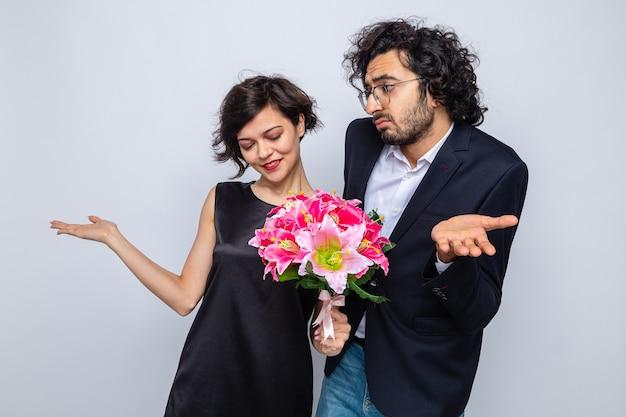 Młoda piękna para mężczyzna i kobieta z bukietem kwiatów uśmiechający się, patrząc zdezorientowany, podnosząc ręce świętując walentynkę