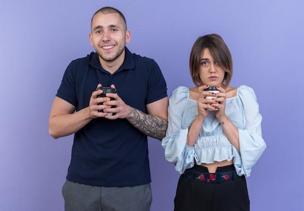 Młoda piękna para mężczyzna i kobieta z papierowymi kubkami wygląda na szczęśliwą i pozytywną uśmiechniętą pozycję