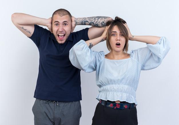 Młoda piękna para mężczyzna i kobieta zdumieni i zaskoczeni z rękami na głowach stojących nad białą ścianą