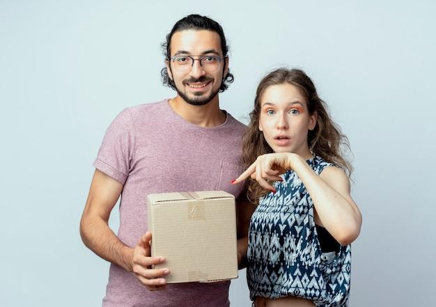 Młoda piękna para mężczyzna i kobiety, mężczyzna trzyma pakiet pudełko uśmiechnięty, podczas gdy jego dziewczyna wskazuje palcem na pudełko zaskoczony na białej ścianie
