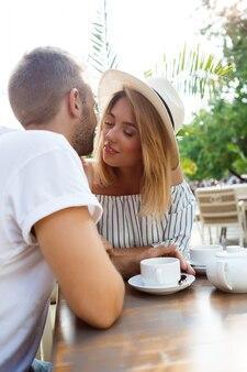 Młoda piękna para mówiąc, uśmiechając się, odpoczynek w kawiarni.