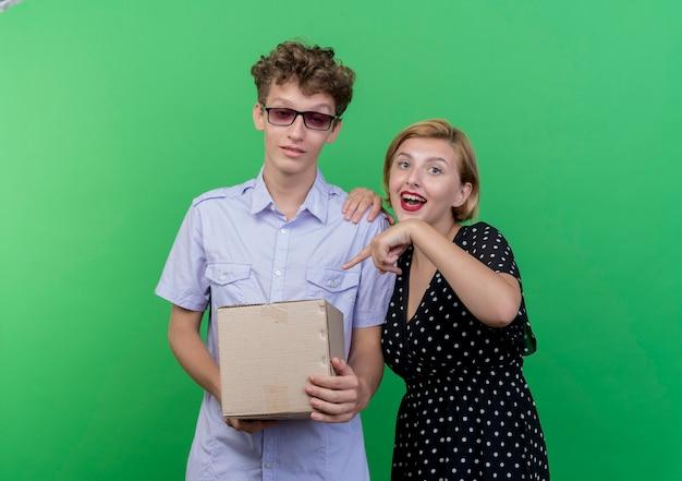 Młoda piękna para mylić mężczyzna trzyma pakiet pudełko, podczas gdy jego dziewczyna wskazuje palcem na pudełko szczęśliwy uśmiechnięty stojący nad zieloną ścianą