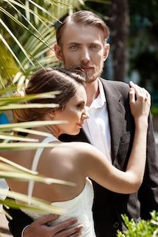 Młoda piękna para nowożeńcy uśmiecha się, obejmując w parku.