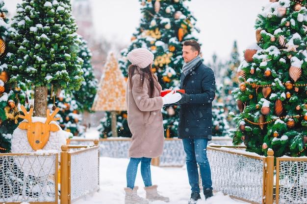 Młoda piękna para obchodzi boże narodzenie na ulicy miasta i daje sobie prezenty