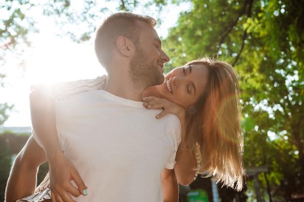 Młoda piękna para ono uśmiecha się, obejmuje, chodzi w parku.