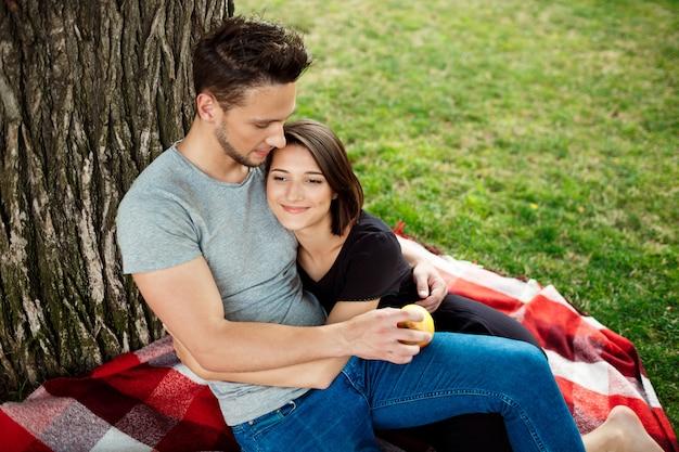 Młoda piękna para ono uśmiecha się, odpoczywający na pinkinie w parku.
