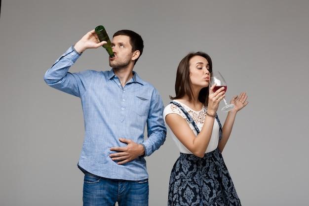 Młoda piękna para pije wino i piwo nad szarości ścianą